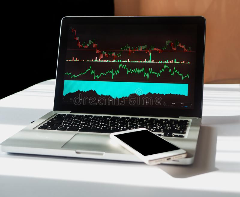 Stock market chart with different indicators on laptop. Phone with copy space on the laptop. Analysis Business Accounting, Statistics Concept royalty free stock image