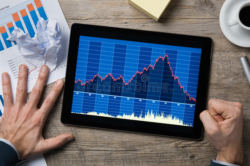 Stock market crash. Top view of decreasing financial graph on digital tablet while businessman slams his fist on the desk. Graph going down on digital tablet on stock image