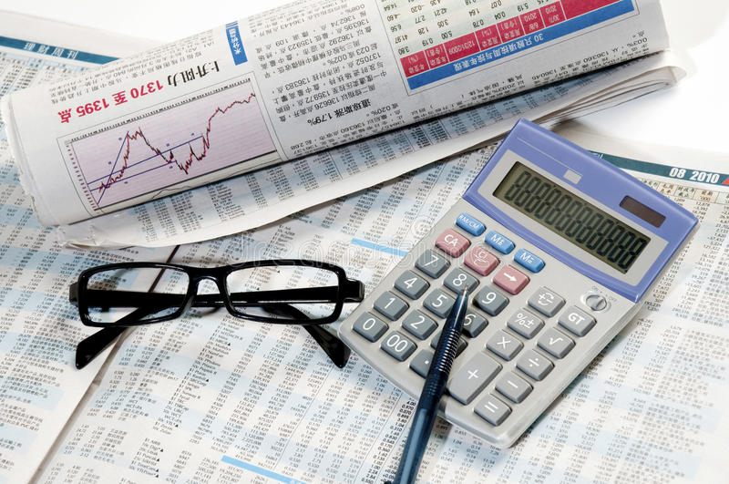 Stock newspapers. Chinese stock newspapers and calculator,pen,glasses stock photography