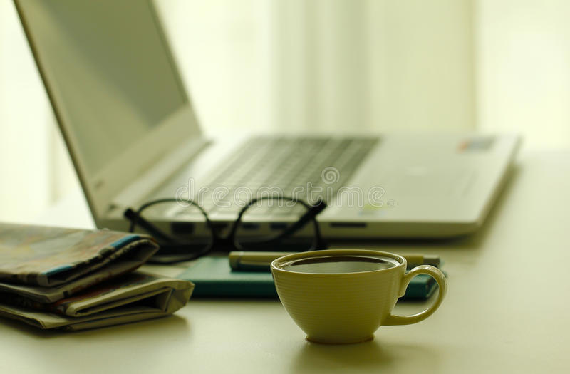 Stock Photo - Coffee, newspapers and laptop in soft focus setting with dramatic ambient light stock image