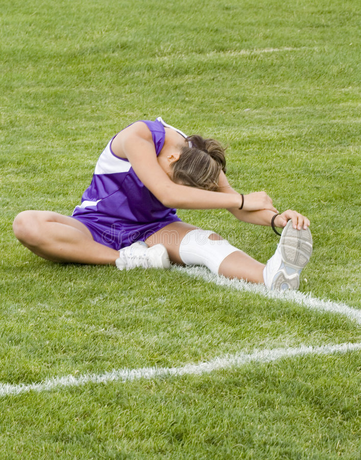 Stock Photo of a Cross Country Runner Stretching. Photo of a girl cross country runner stretching in a purple uniform royalty free stock images