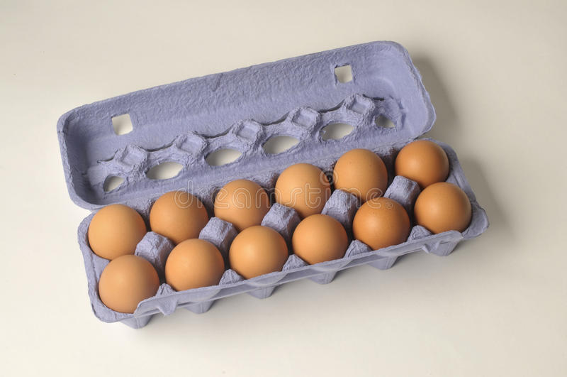 Stock Photo of Dozen Eggs. This is a photo of dozen brown eggs in a blue carton of on a white background stock photo
