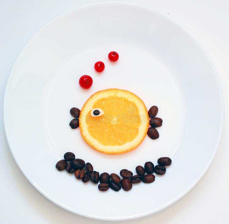 Food art. Little fish from fruit, creative idea for healthy breakfast on the white plate stock images