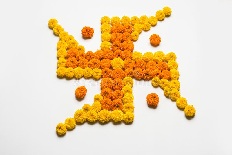 Stock photo of hindu auspicious symbol called Swastika made using marigold flower or zendu or genda phool, Flower rangoli in the s. Hape of Swastika for diwali/ stock image