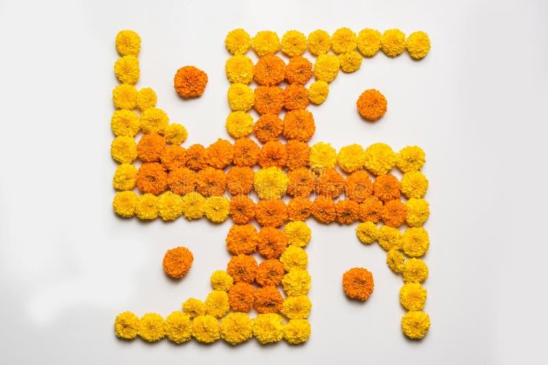 Stock photo of hindu auspicious symbol called Swastika made using marigold flower or zendu or genda phool, Flower rangoli in the s. Hape of Swastika for diwali/ royalty free stock photos