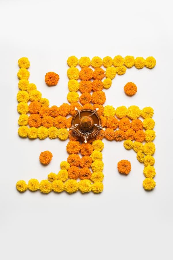 Stock photo of hindu auspicious symbol called Swastika or swastik made using marigold flower/zendu/genda phool & diwali diya / cla. Y lamp, Flower rangoli in the royalty free stock image