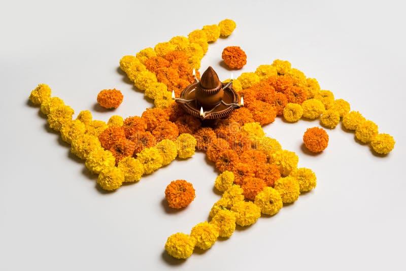 Stock photo of hindu auspicious symbol called Swastika or swastik made using marigold flower/zendu/genda phool & diwali diya / cla. Y lamp, Flower rangoli in the stock image
