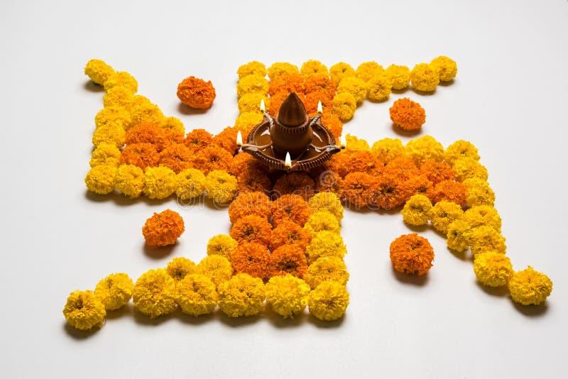 Stock photo of hindu auspicious symbol called Swastika or swastik made using marigold flower/zendu/genda phool & diwali diya / cla. Y lamp, Flower rangoli in the royalty free stock photos