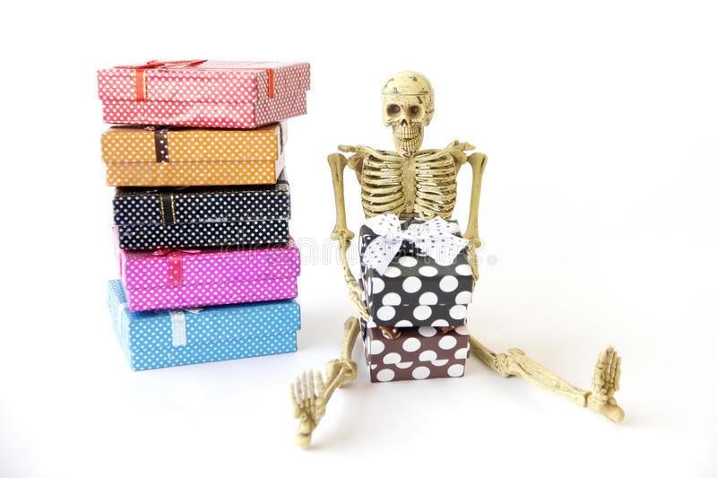 Stock Photo: Human skeleton Sit on the floor with gift box. royalty free stock images
