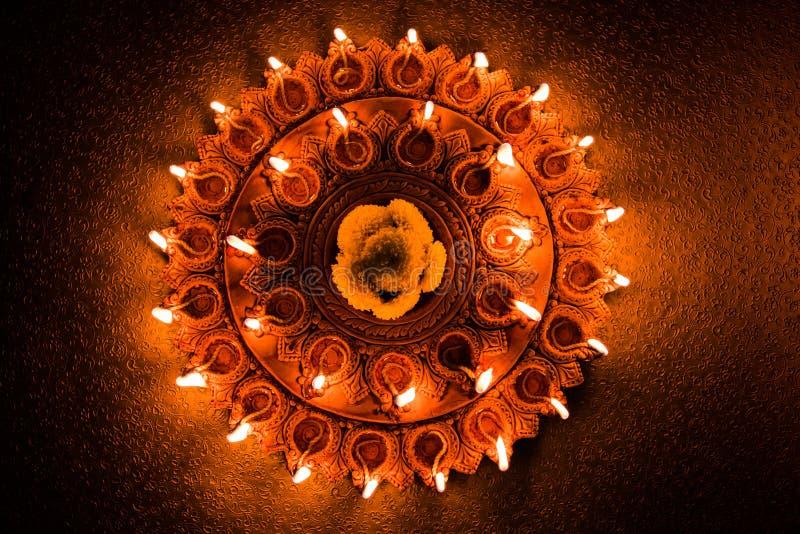 Stock photo of illuminated Diwali diya or oil lamp light, selective focus. Stock Photo of an illuminated terra-cotta Diwali lamp or Diya with detailed artwork on royalty free stock photo