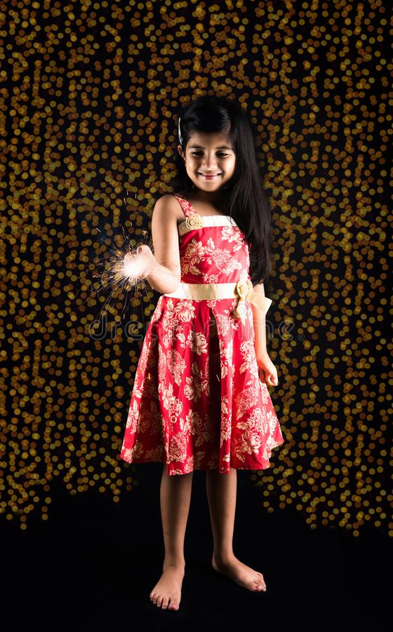 Stock photo of indian little girl holding fulzadi or sparkle or fire cracker on diwali night stock photography
