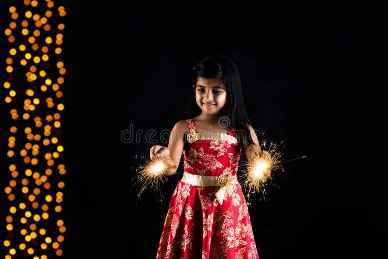 Stock photo of indian little girl holding fulzadi or sparkle or fire cracker on diwali night stock image