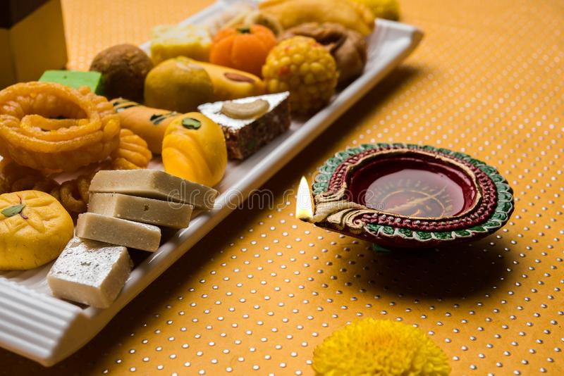 Indian sweets or Mithai for diwali festival with oil lamp or diya and gift box. Stock photo of Indian sweet or mithai and oil lamp or diya with gift box and royalty free stock images