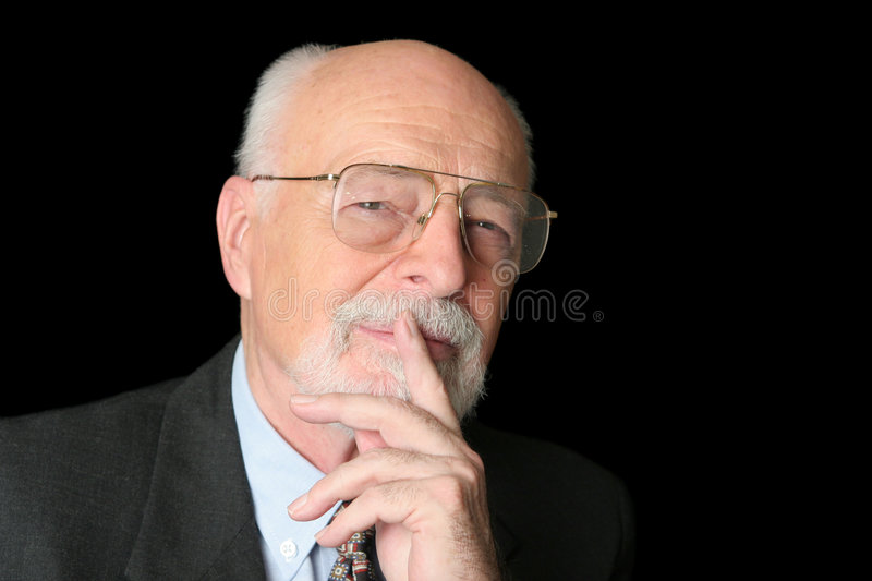 Stock Photo of Intelligent Senior Man. An intelligent senior man with a thoughtful expression over a black background stock image