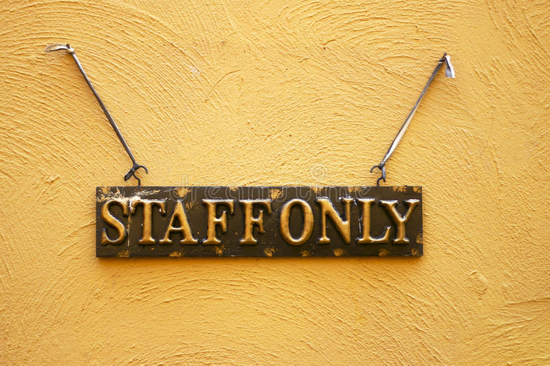 Stock Photo - Staff only door sign board isolated on Cement wall. Staff only hanging sign on Cement wall royalty free stock image