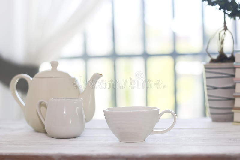 Stock Photo:Tea set including a teacup, a teapot and a sugar bo. Little white tea cup and a kettle isolated over side windows background stock photos