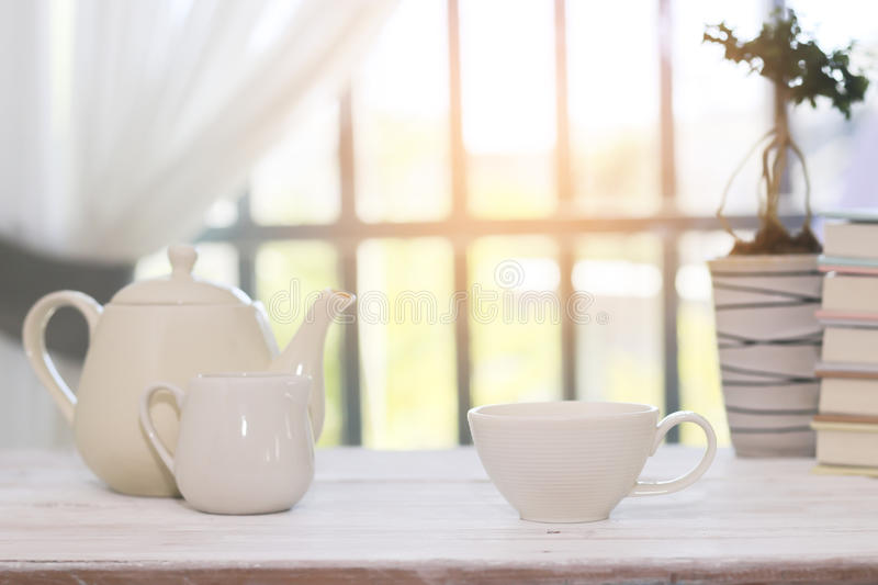 Stock Photo:Tea set including a teacup, a teapot and a sugar bo. Little white tea cup and a kettle isolated over side windows background stock photography