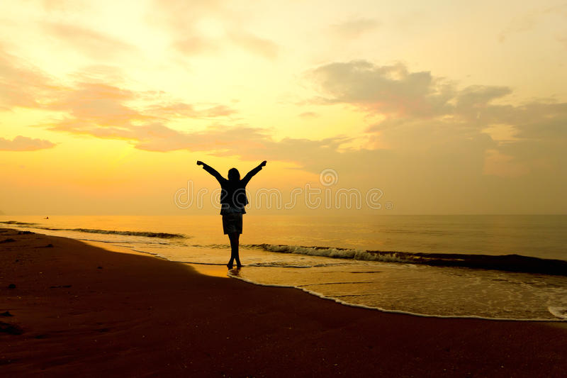 Stock Photo: woman open arms under the sunset at sea. Woman open arms under the sunset at sea stock photos