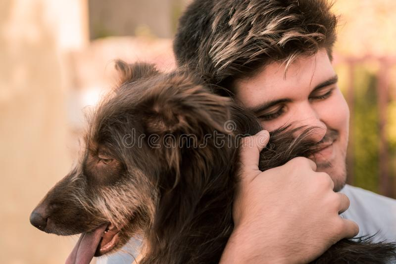 Stock photo of a young man hugging a brown dog, friendly concept animal, best friends. Young man hugging a brown dog, friendly concept animal. Best friend of stock photo