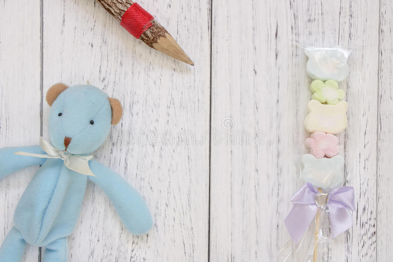 Stock Photography flat lay vintage white painted wood table blue. Bear doll cotton candy pencil royalty free stock images