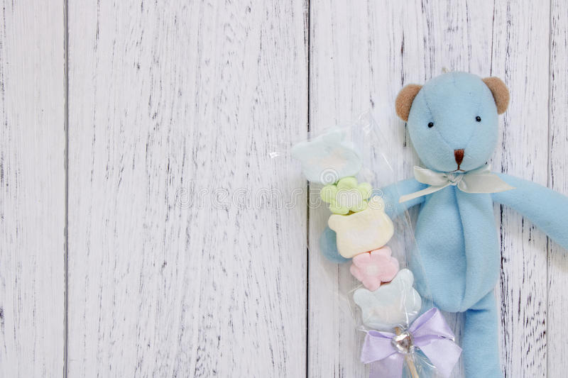 Stock Photography flat lay vintage white painted wood table blue. Bear doll holding cotton candy stock images