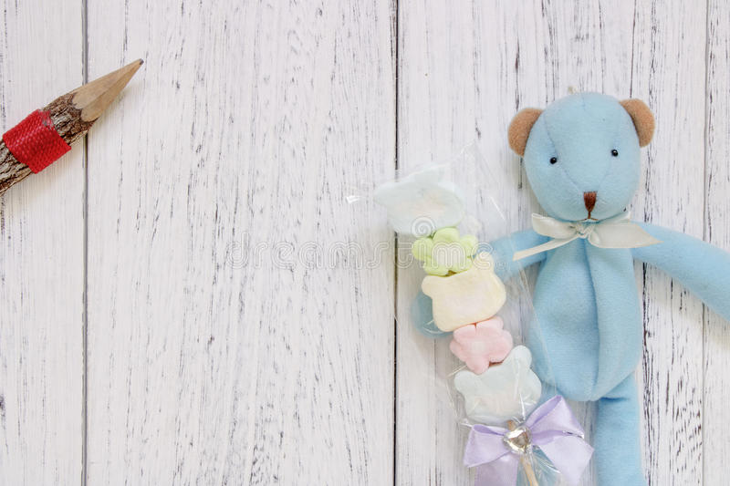 Stock Photography flat lay vintage white painted wood table blue. Bear doll holding cotton candy pencil stock photos