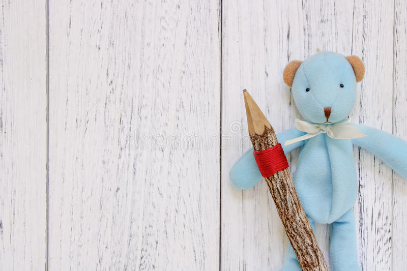 Stock Photography flat lay vintage white painted wood table blue. Bear doll holding pencil stock photo