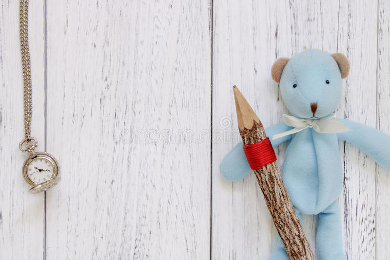 Stock Photography flat lay vintage white painted wood table blue. Bear doll holding pencil pocket clock stock image