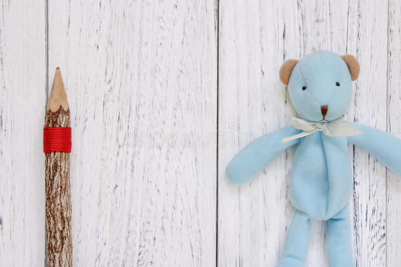 Stock Photography flat lay vintage white painted wood table blue. Bear doll pencil stock photo