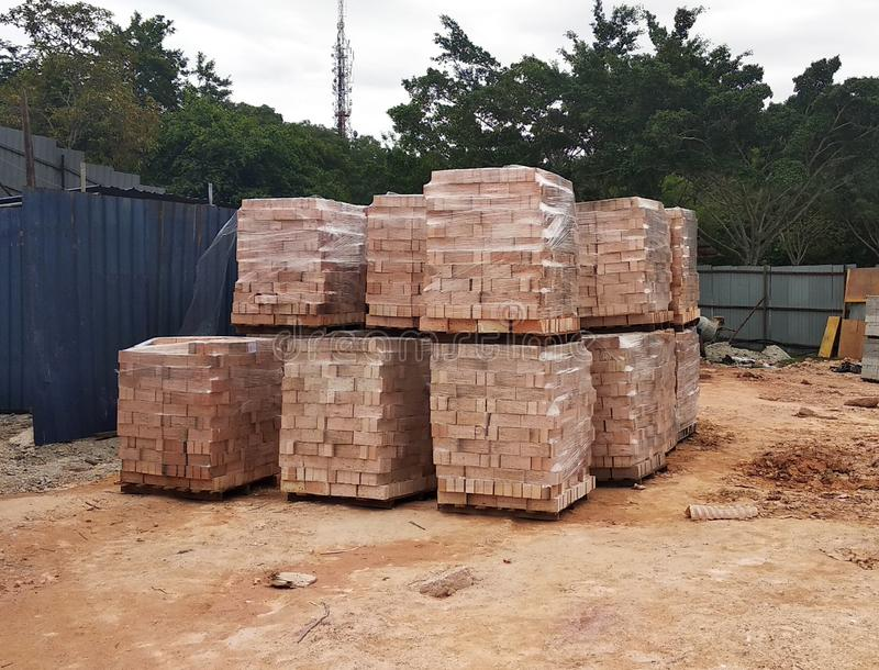 Stock pile of clay brick on wooden pallets stacked at the construction site. royalty free stock photos