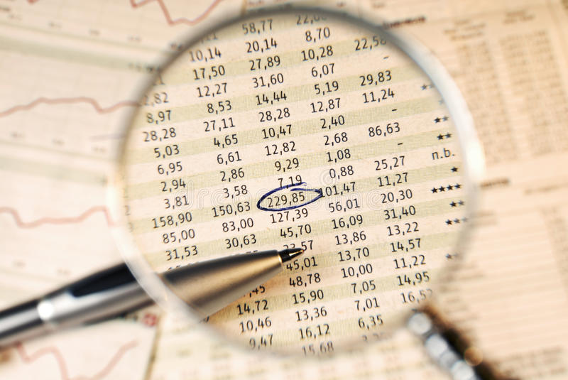 Stock prices in the focus. Magnifier shows stock prices. One is marked stock photography