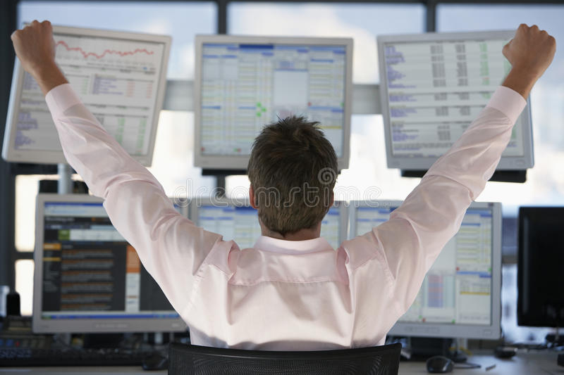 Stock Trader Watching Computer Screens With Hands Raised. Rear view of stock trader with hands raised looking at multiple computer screens royalty free stock images