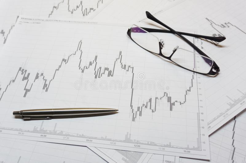 Stock trading chart. Stock trading candle stick chart analysis, glasses and pen closeup stock photo