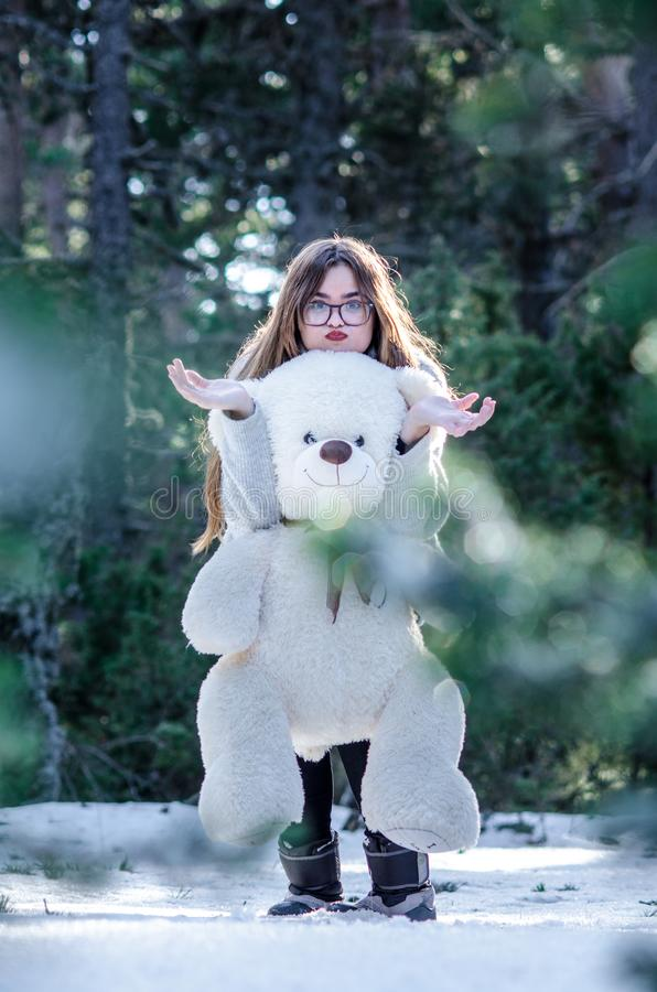 Blonde girl hugging the bear with funny face and gesture while looking at the camera. Photography in the snowy forest on a cold royalty free stock photos