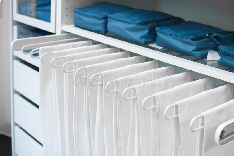 Stockage des choses dans le cabinet et de l'ordre dans la maison Choses blanches accrochant d'une manière ordonnée sur un cintre  image stock