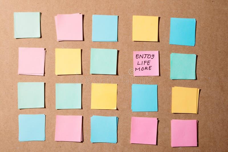 Stockbriefpapier mit Text - Genießen Sie das Leben, das auf hölzernem Hintergrund für glücklich ist, Ihre Gedächtnisstilllebenart lizenzfreie stockfotografie