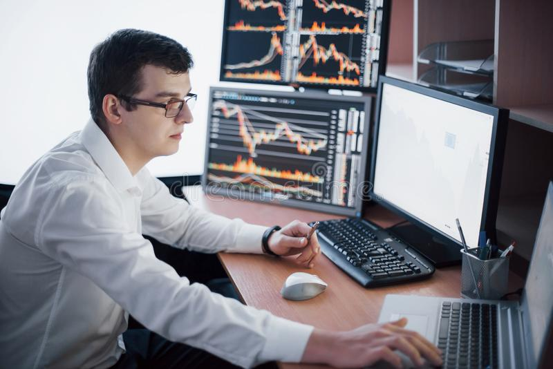 Stockbroker in shirt is working in a monitoring room with display screens. Stock Exchange Trading Forex Finance Graphic stock image