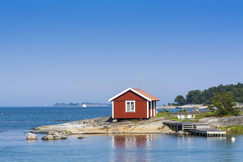 Stockholm archipelago: small red summerhouse. Small red summerhouse and jetty on a small skerrie called Lilla Skarvgrundet at Långvik, Möja in Stockholm stock photos