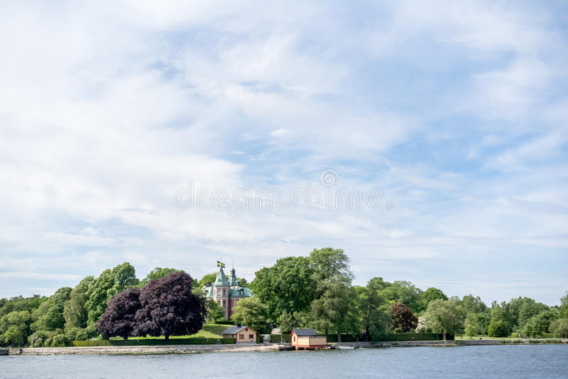 STOCKHOLM, SCHWEDEN - 6. JUNI 2016: Küstenansicht eines alten kleinen Schlosses mit schwedischen Flaggen auf einer Insel von Stoc lizenzfreies stockbild