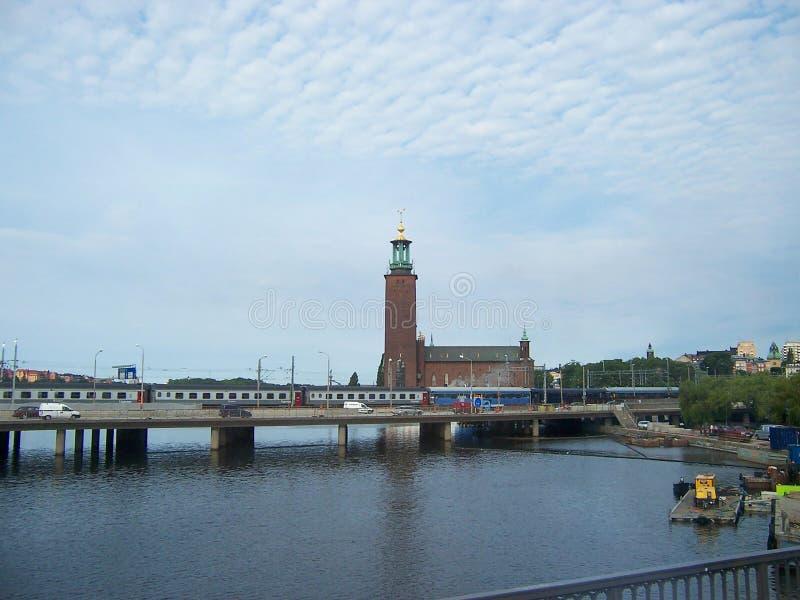 Stockholm Sverige - Juli, 2007: stads- landskap med sikter av stadshuset, floden och bron på som drevet och bilarna arkivbilder