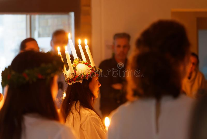Lucia parade with singing girls and boys in white dresses holding candles. Traditional celebration of the suffering of saint. STOCKHOLM, SWEDEN - DEC 13, 2017 stock image