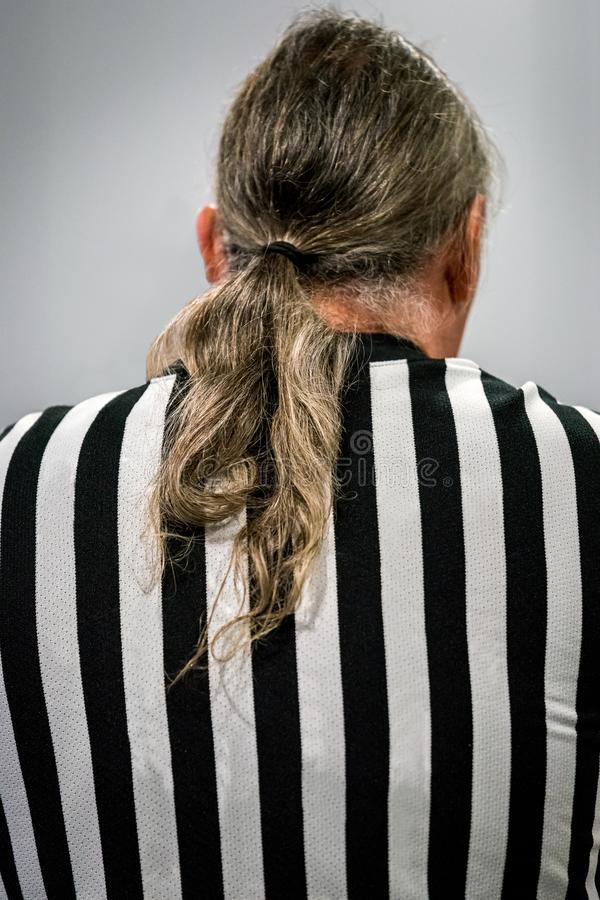 Back view of a male referee with ponytail hair. STOCKHOLM, SWEDEN - JANUARY 13, 2018: Back view of a male referee with ponytail hair in black and white striped stock photo
