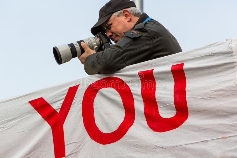Senior male taking photographs using a long lens. Leaning on a large sign with the word You. royalty free stock image