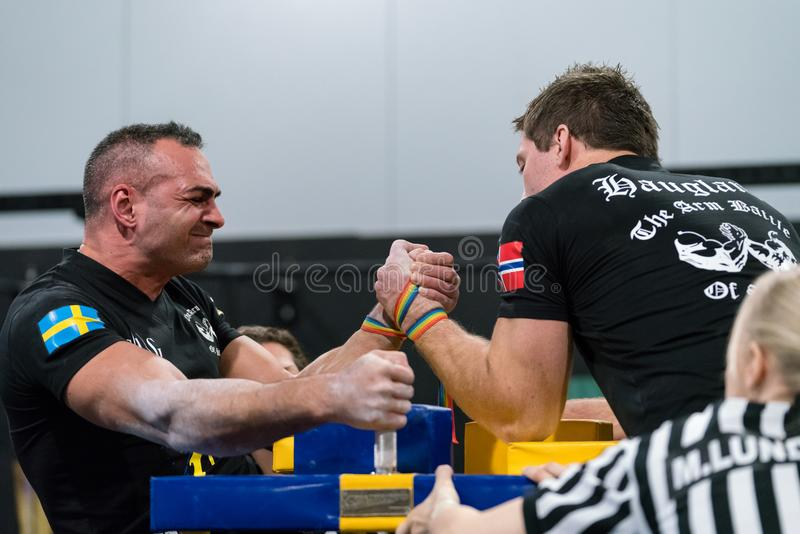 Two male arm wrestlers in a tough fight. STOCKHOLM, SWEDEN - JANUARY 13, 2018: Profile view of a Swedish and Norwegian male arm wrestler and a referee in a royalty free stock photo