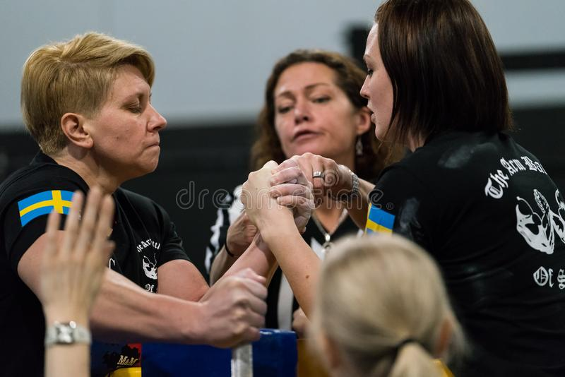 Two Swedish arm wrestlers in tough fight. STOCKHOLM, SWEDEN - JANUARY 13, 2018: Profile view of two Swedish female arm wrestlers and one referee in a match at royalty free stock photos