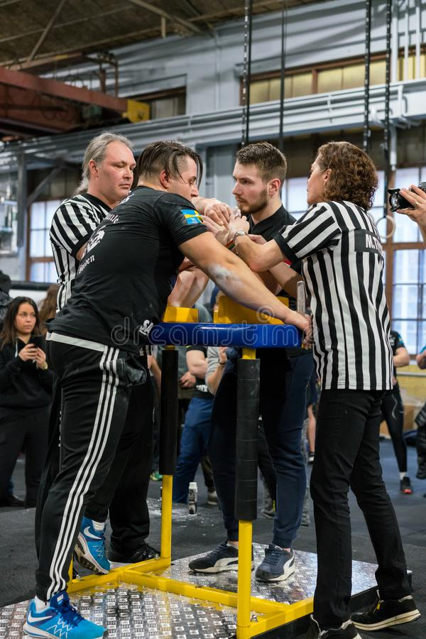 Two male arm wrestlers and referees in a tough fight. STOCKHOLM, SWEDEN - JANUARY 13, 2018: Two referees adjusting the hands on a Swedish and Latvian male royalty free stock images