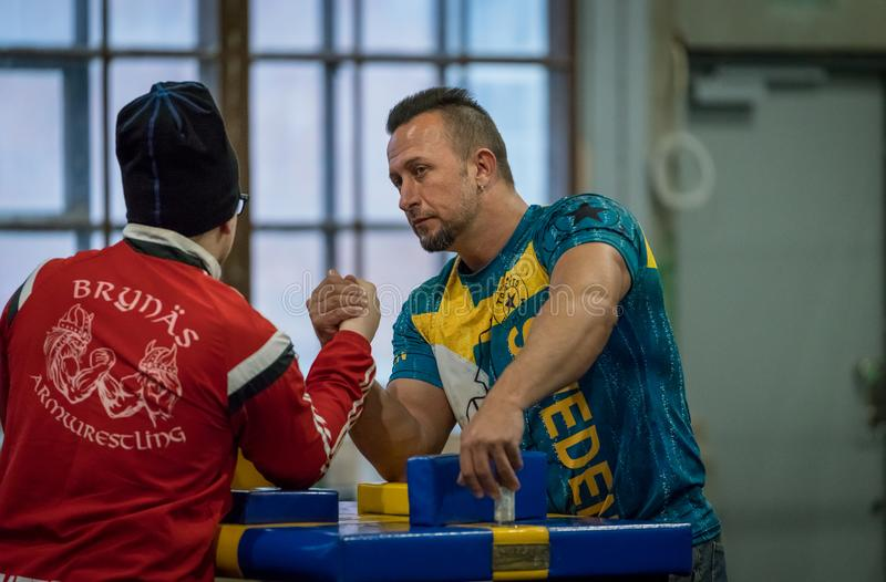 Two Swedish arm wrestlers in a friendly fight. STOCKHOLM, SWEDEN - JANUARY 13, 2018: Two Swedish male arm wrestlers training in a friendly match during the stock images