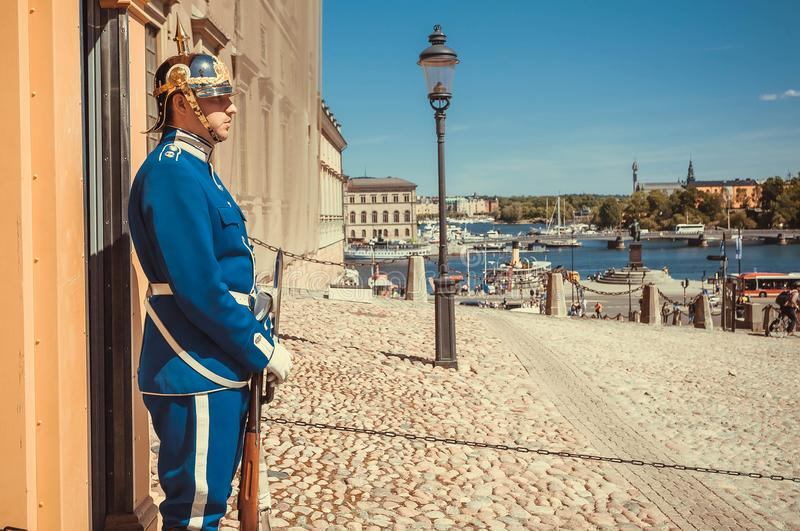 Soldier of Royal Guards standing in uniforms and silver helmets on square of Old Town royalty free stock image