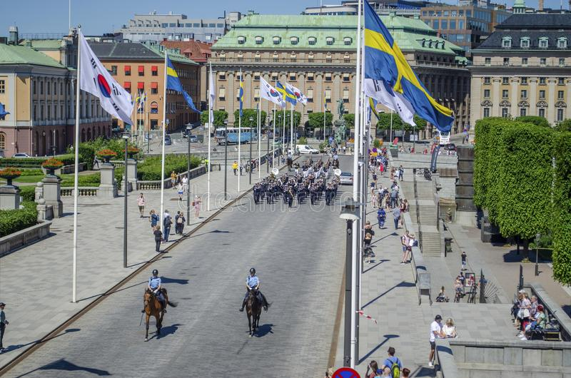 Stockholm, Sweden - June 15, 2019 Group of uniformed national guard marching on the street followed by two horsemen in Stockholm. While tourists are taking stock image
