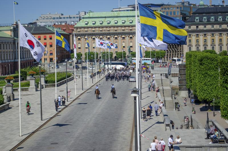 Stockholm, Sweden - June 15, 2019 Group of uniformed people marching on the street followed by two horsemen. In Stockholm stock photos